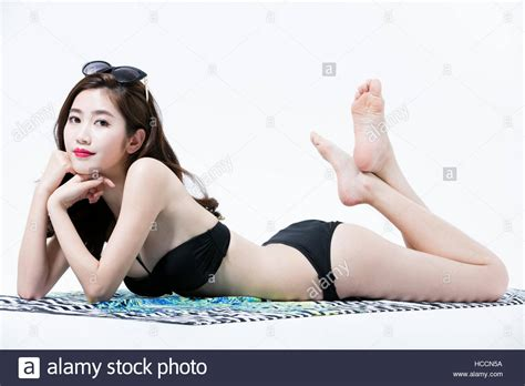 Side view of young woman in bikini lying face down on mat